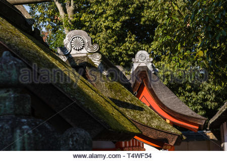 Detail of a traditional Japanese thatched roofs with Kamon ceramic tiled decorative end caps on the grounds of the Fushimi Inari Taisha Shinto shrine, - Stock Image