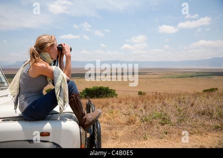 Tanzania, Ngorongoro. A tourist looks out over the Ngorongoro Crater from the bonnet of her Land Rover. MR. - Stock Image