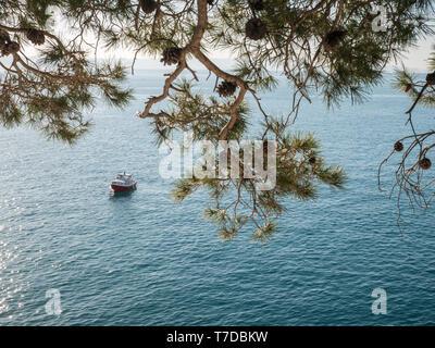 Small boat on calm blue sea near shore on sunny summer day - Stock Image