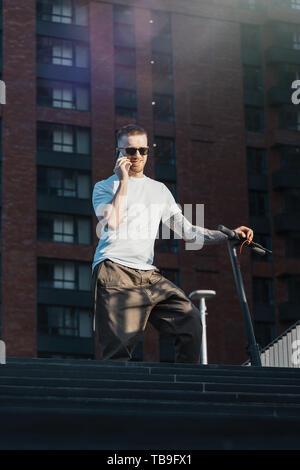 Attractive man talking by mobile phone and standing next to electric kick scooter at modern buildings or commercial centres background. Man is on fore - Stock Image