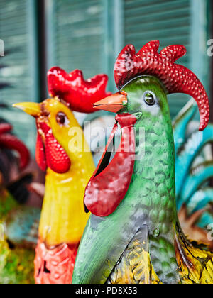 Metal garden art or yard decorations of colorful farm roosters for sale at a roadside farmer's market in Pike Road Alabama, USA. - Stock Image