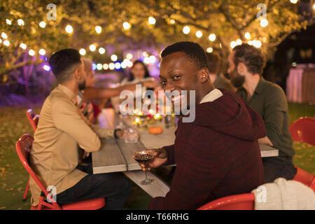 Portrait smiling man drinking wine, enjoying dinner garden party - Stock Image