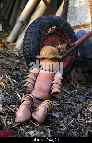 Terracotta flowerpot man leaning against wheelbarrow wheel - Stock Image