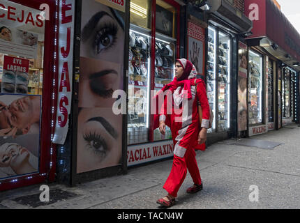 A Muslim woman in a brightly colored dress and hijab walking past an eyebrow salon under the elevated subway on Roosevelt Ave. in Jackson Heights, NYC - Stock Image