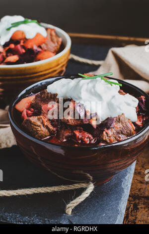 Two bowls of Borscht soup with hearty, meaty chunks of beef, root vegetables, cabbage and beets. Served with sour cream and chives, - Stock Image