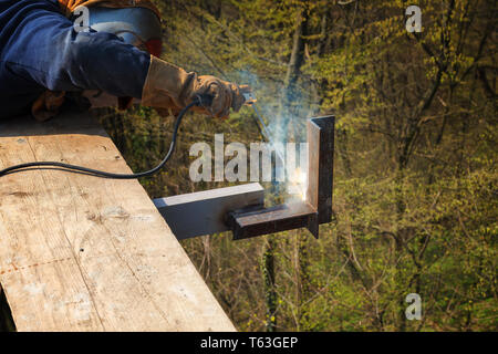 Welding work, welder welding metal material in heavy industry manufacturing - Stock Image