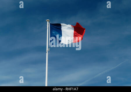 French flag in the wind against a cloudy blue sky background - Stock Image