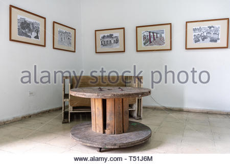 'El Mejunje de Silverio' indoors details of the famous place and tourist attraction. Rustic table and seats with gallery art in the wall. The local la - Stock Image