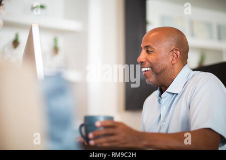 African American man working from his home office. - Stock Image