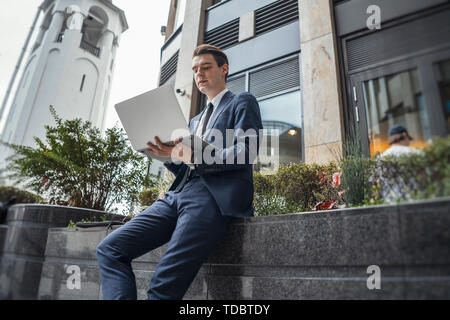 Close up of businessman working on a laptop next to business center and skyscraper at downtown. - Stock Image