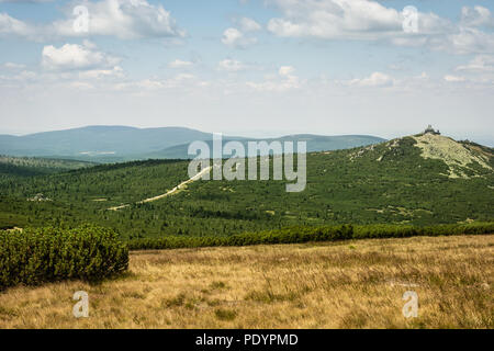 Cloudy blue sky, rocky green hill and yellow grass in the Giant Mountains in Poland, Central Europe - Stock Image