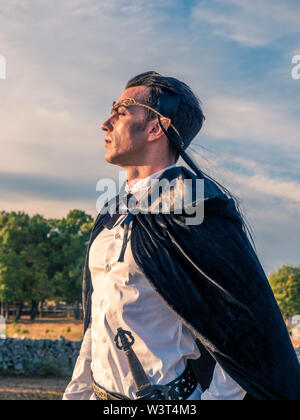 Brown-haired man with elf ears, tiara on head and black cape, looks forward - Stock Image