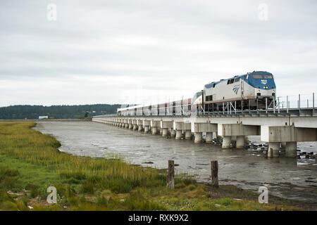 An Amtrak Cascades train crosses Mud Bay in Surrey, British Columbia, Canada - Stock Image