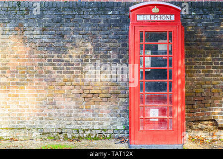 Traditional red telephone box on street of Hampstead Heath in London against a grungy brick wall - Stock Image