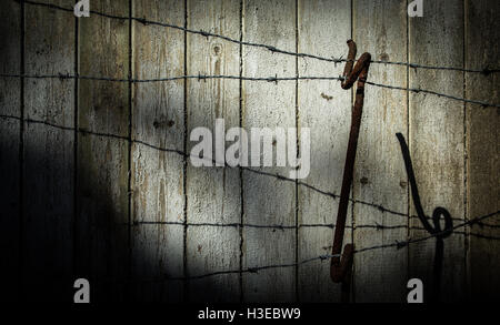 Strands of a barbed wire fence and support from WWI days against the faded planks of an old wooden fence with ominous - Stock Image