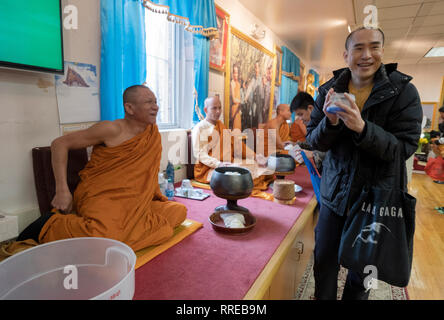 A Buddhist worshipper shares a pleasant moment with a monk after bringing the monk food for his lunch. In Elmhurst, Queens, New York - Stock Image
