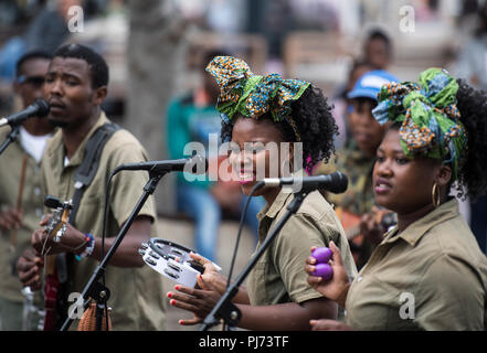 A band of singers and musicians entertaining tourists on the streets of Cape Town, South Africa - Stock Image