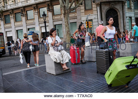 People sitting on La Rambla Street in the City of Barcelona in Catalunya in Spain in Europe - Stock Image