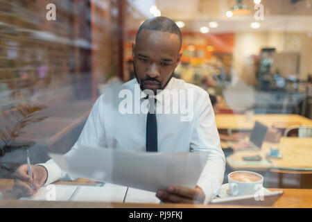 Focused businessman reviewing paperwork, working in cafe window - Stock Image