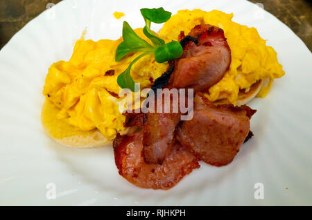 Breakfast snack in Yorkshire a toasted English muffin with two slices of fried bacon and scrambled egg - Stock Image