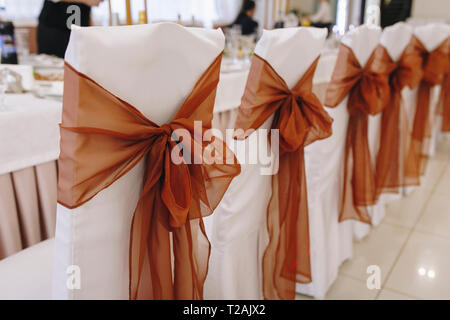 Ribbon tied to dining chairs at wedding - Stock Image