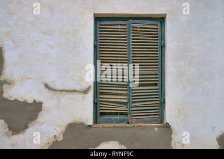 Minimalist capture of a single rural window on a white textured wall with plaster repairs.  Window has dark grey shutters in a state of needing repair - Stock Image