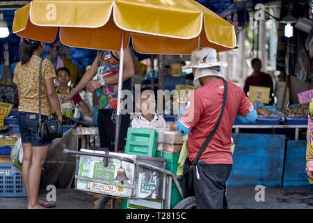 Child buying ice cream from a Thailand icecream vendor - Stock Image