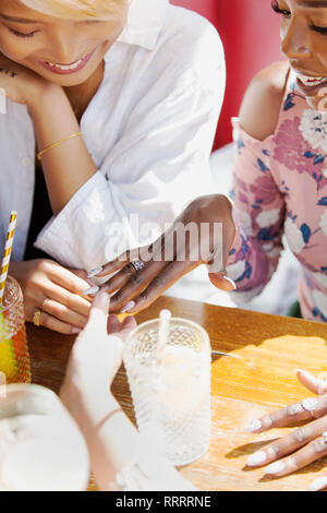 Young women friends looking at manicured fingernails - Stock Image