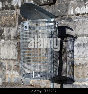 Empty waste bin made of silver colored metal net. Photographed with grey stonewall. Photo was taken outdoors during a sunny day. - Stock Image