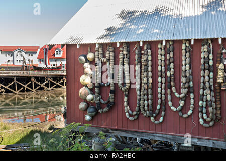 Old net floats decorate the wall of an old wooden boathouse along Hammer Slough in Petersburg, Mitkof Island, Alaska. Petersburg settled by Norwegian immigrant Peter Buschmann is known as Little Norway due to the high percentage of people of Scandinavian origin. - Stock Image