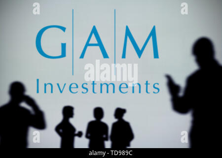 The GAM Investments logo is seen on an LED screen in the background while a silhouetted person uses a smartphone in the foreground (Editorial use only - Stock Image