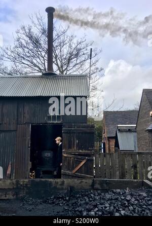 Workman at a coal driven boiler house,  Blists Hill, Ironbridge Gorge, Shropshire, England - Stock Image