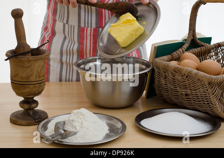 Person baking a cake, adding the butter to a bowl & surrounded by the other ingredients - Stock Image