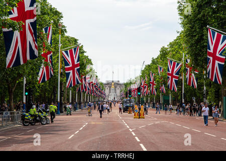 London, England, UK - June 1, 2019: Union Jack flags fly along The Mall ahead of a ceremonial event in central London, while crowds of tourists walk o - Stock Image