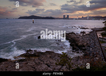 Seascape in Busan, South Korea, at dusk with city lights in the far horizon. - Stock Image