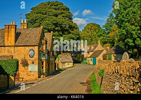 Street scene in the pretty Cotswold village of Snowshill on a summer afternoon, with the Snowshill Arms public house - Stock Image