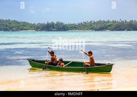 Vavau island, Tonga - Jan 1 2014: Three local native indigenous Polynesian boys rowing in a canoe, Vava'u island, Tonga, Polynesia, Oceania, South Pac - Stock Image