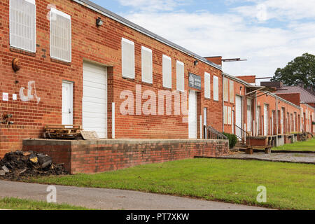 HICKORY, NC, USA-9/18/18:  A line of low loading docks and bay doors of an old industrial building. - Stock Image