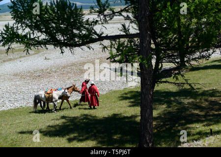 Naadam Festival in Khatgal, Mongolia.Two horse riders with their horses - Stock Image