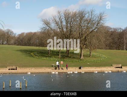 People walking alongside Waterloo Lake with spring flowers behind, in Roundhay Park, Leeds, West Yorkshire, England, UK - Stock Image