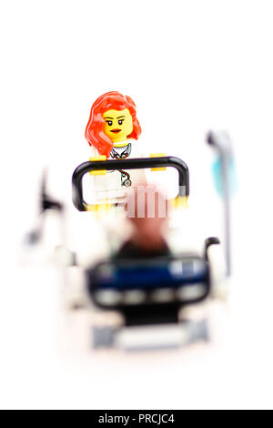 Lego nurse pushes a patient in a hospital bed. - Stock Image
