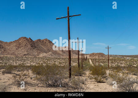 Old disused road on the California and Arizona border lined with telegraph poles. - Stock Image