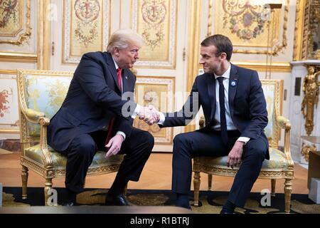 U.S President Donald Trump, left, and French President Emmanuel Macron shake hands before the start of a during a bilateral meeting at the Elysee Palace November 10, 2018 in Paris, France. Trump is in France for commemorations marking the Centennial of the end of World War I. - Stock Image