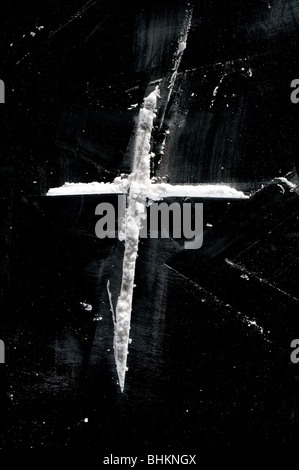 image of lines of cocaine powder in shape of cross on black surface - Stock Image
