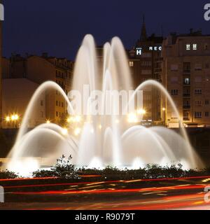 Spain, Asturias, Oviedo, night view of an artificial fountain on a roundabout in town - Stock Image