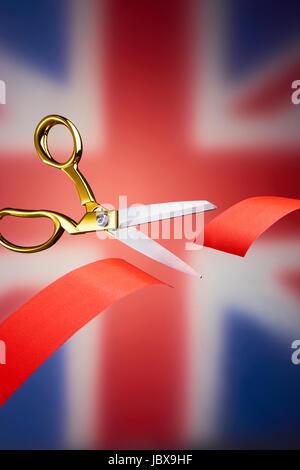 Golden scissors cutting red ribbon, symbolising brexit - Stock Image