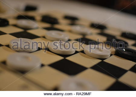 Closeup of drafts (checkers) pieces on a wooden gaming board. Drafts is similar to chess however with fewer rules is easier to pick up and play. - Stock Image