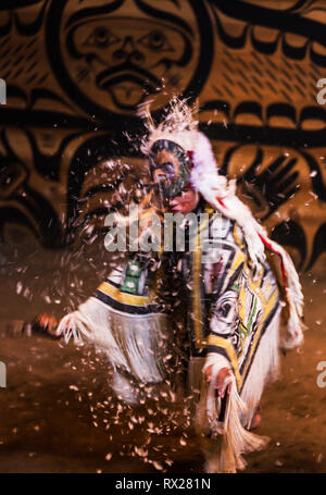 Eagle down escapes from the headdress of a young Kumugwe Dancer performing the 'Holixkyla'  or chief dance during Aboriginal Days in the Komok's bigho - Stock Image