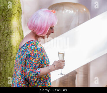 A lady with a pink wig and a glass of prosecco at Latitude Festival 2018. - Stock Image