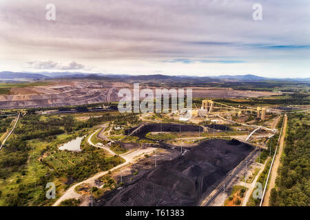 Huge open cut black coal mine in Hunter Valley rural region of Australia excavating fossil fuel for electrisity power station in elevated aerial view  - Stock Image
